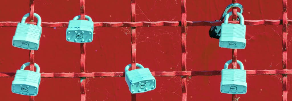 Padlocks on a fance in front of a red wall